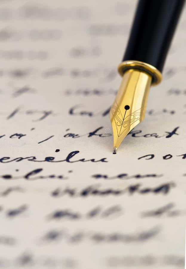 Calligraphy concept, fountain pen on a handwritten letter. Calligraphy concept, shiny gold fountain pen on a handwritten letter stock photography