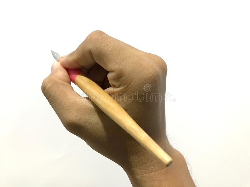 Calligraphy dip pen holder tool. Hand holding a calligraphy oblique pen tool with wooden holder and pointed nib showing correct hold position and finger royalty free stock photo