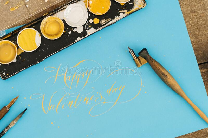 Calligraphy and inscription. Happy valentines day, on a blue background with gold ink.  stock photos