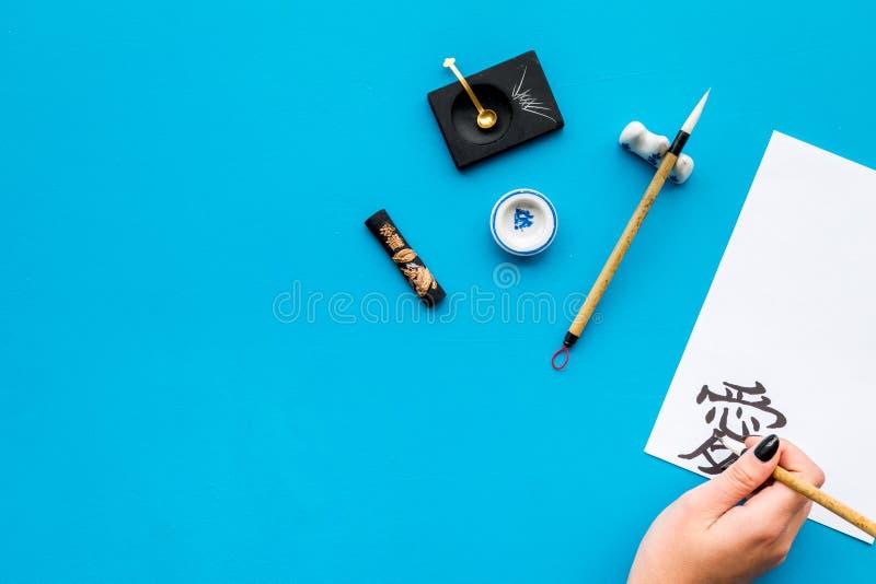 calligraphy A mão escreve o amor do hieróglifo no Livro Branco no espaço azul da cópia da opinião superior do fundo imagens de stock