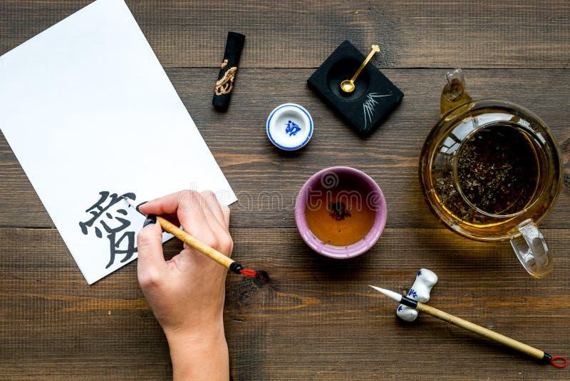 calligraphy A mão escreve o amor do hieróglifo no Livro Branco na opinião superior do fundo de madeira escuro imagem de stock royalty free