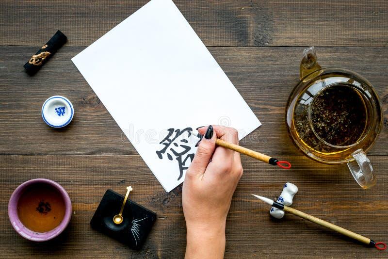 calligraphy A mão escreve o amor do hieróglifo no Livro Branco na opinião superior do fundo de madeira escuro fotos de stock