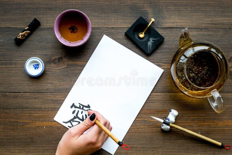calligraphy A mão escreve o amor do hieróglifo no Livro Branco na opinião superior do fundo de madeira escuro imagens de stock royalty free