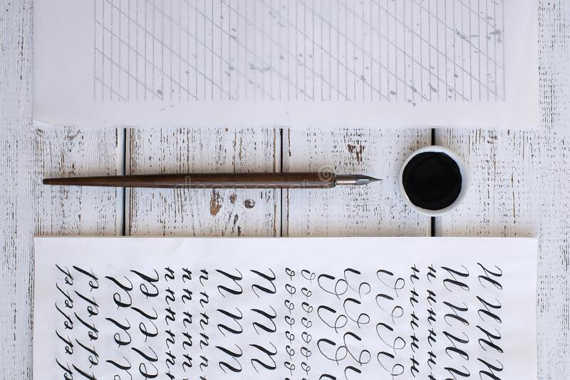 Calligraphy sheets, nibs, paper, ink on a wooden background. Letters of the English alphabet written with a paint brush. Calligraphy sheets, nibs, paper, ink on stock image