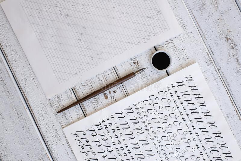 Calligraphy sheets, nibs, paper, ink on a wooden background. Letters of the English alphabet written with a paint brush. Calligraphy sheets, nibs, paper, ink on stock photo