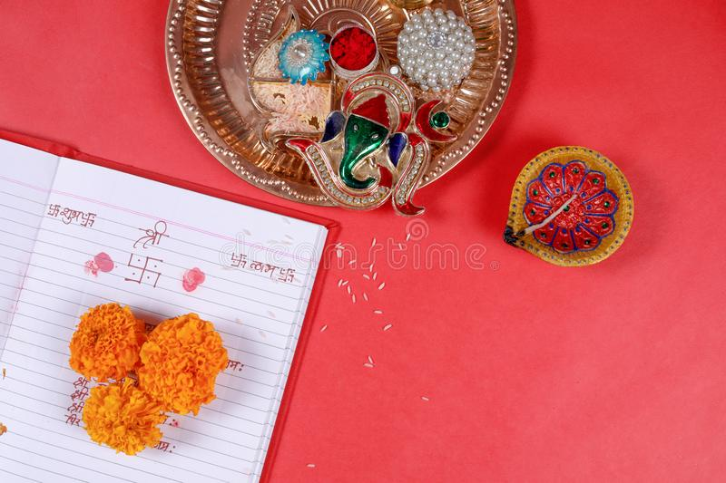 Calligraphy writing in hindi Shubha Labh means Goodness & Wealth, over Red accounting note book , diya, stock photos