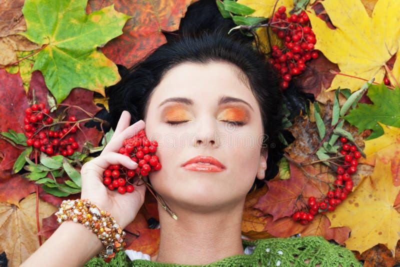 Calling autumn. Girl calling autumn using bunch of rowan royalty free stock photography