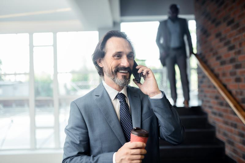 Man holding coffee smiling while calling colleague royalty free stock images
