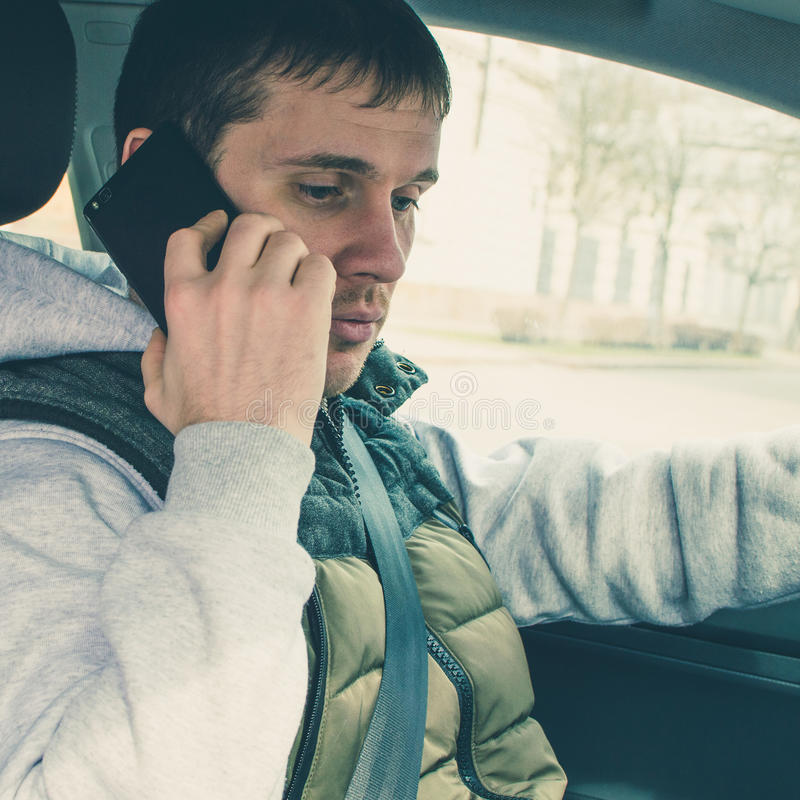 Calling by driving. Risky driver using phone while driving. square stock photography