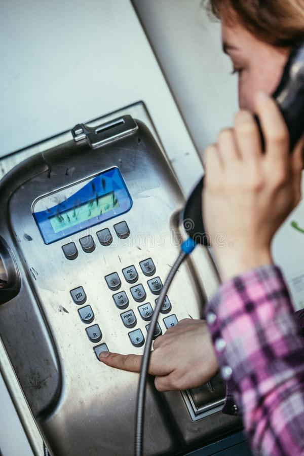 Calling home in the holidays: Young girl speaks in an old fashioned pay phone royalty free stock image