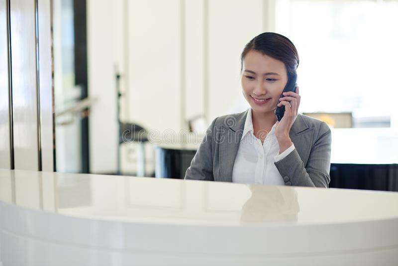 Calling receptionist. Vietnamese young female receptionist talking on phone royalty free stock photography