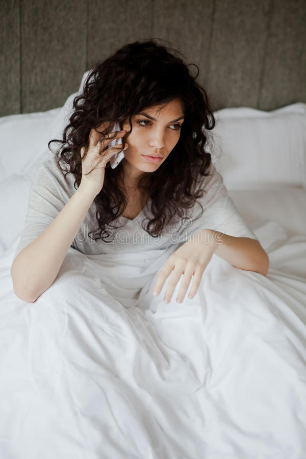 Calling in sick. Woman calling in sick in the morning from her bed stock photo