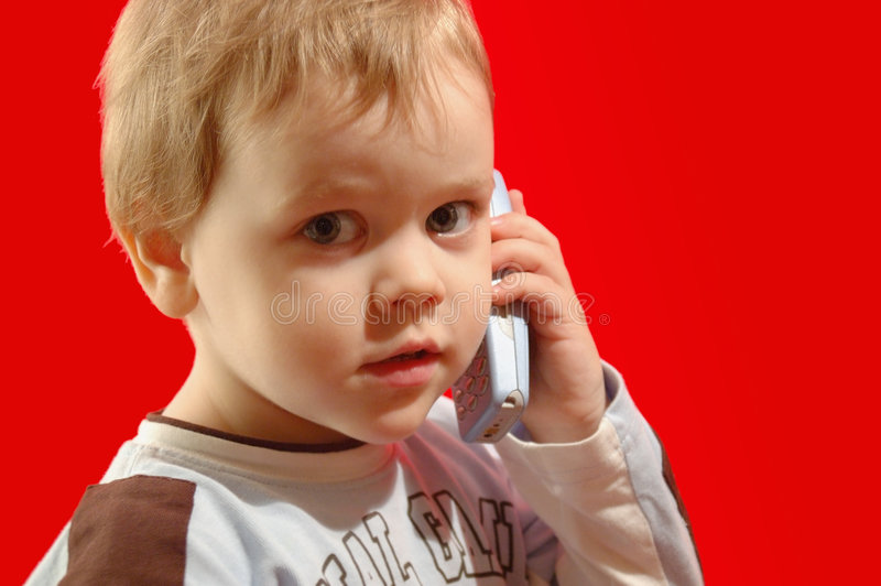Calling to mom. Small kid holding a mobile phone to his ear, bright red background. Calling to mom or 911, for example. Admins: I hope the text on the shirt does stock images