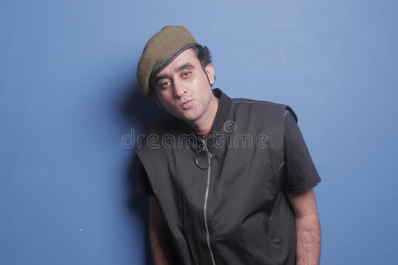So callled army boy, portrait of army getup. Guy infront of blue background, wearing black jacket, army cap stock photos