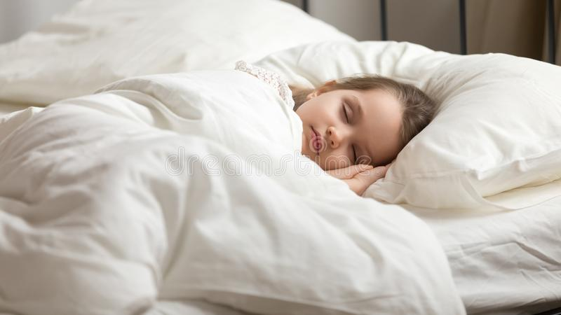 Sweet little kid girl having healthy day nap in bed. Calm adorable little daughter take day nap. Tranquil preschool child girl covered with white fresh duvet royalty free stock images