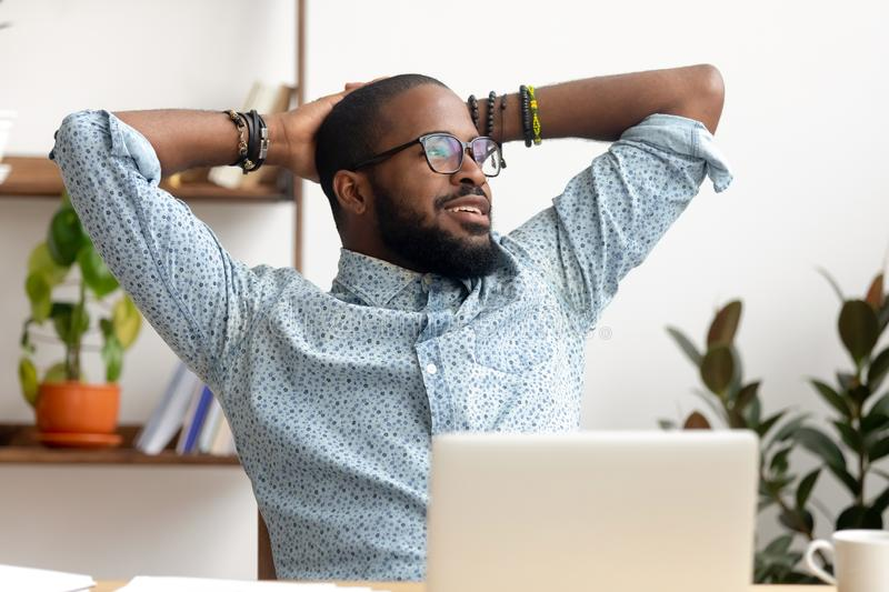 Calm african businessman take break at workplace relaxing finished work. Calm african american business man take break at workplace relaxing finished work, happy stock photos