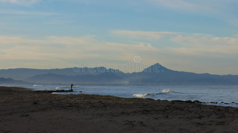 Calm afternoon at the beach in Denia, Spain. Empty beach on a winter day. Scene in Denia, Spain stock photography