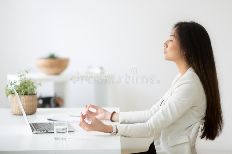 Calm Asian employee meditating in office relieving work stress royalty free stock photo