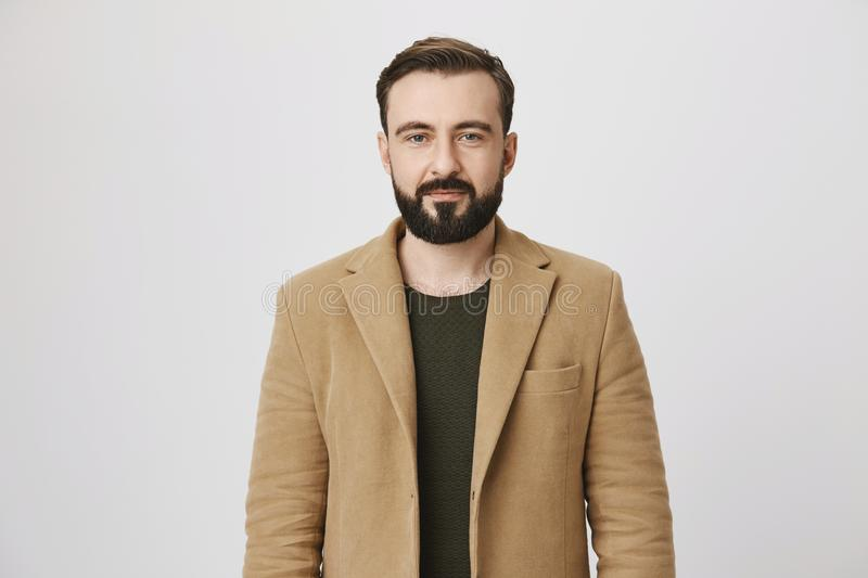 Calm attractive bearded person in coat over green pullover with normal expression, standing against gray background. Man stock photo