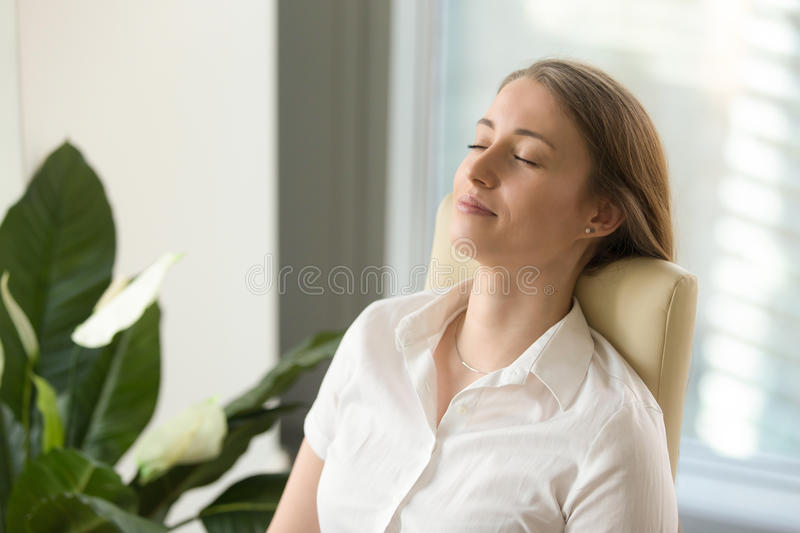 Calm attractive woman feeling relaxed leaning back on office cha. Calm attractive woman feeling relaxed in office home, peaceful mindful businesswoman leaning royalty free stock photography