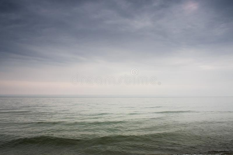 Calm Baltic sea in windless summer day in Latvia. Calm Baltic sea with foggy horizon and scenic skies with clouds in windless summer day in Latvia royalty free stock photography