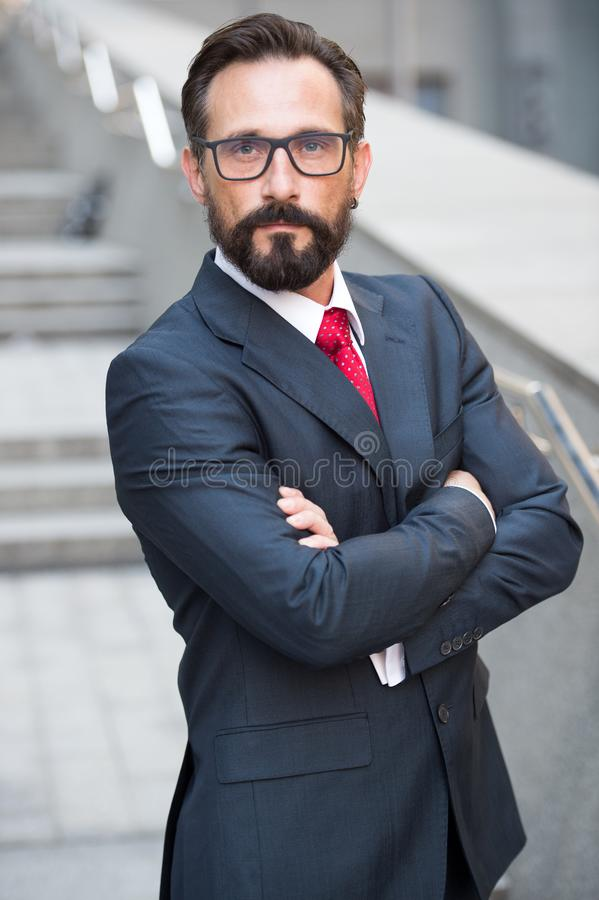 Calm bearded manager keeping hands in crossed position. Shrewd glance. Waist up of confident bearded businessman being calm while keeping hands in crossed royalty free stock images