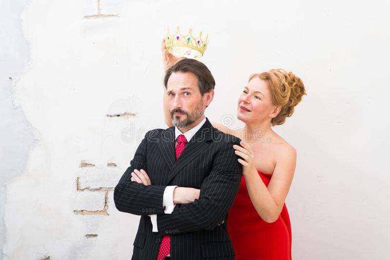 Waist up of elegant woman holding golden crown above her mans head stock image