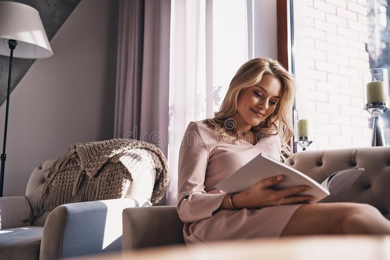Calm and beautiful. Attractive young woman reading magazine and royalty free stock image