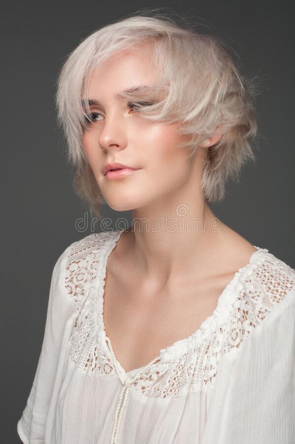 Calm beautiful blonde in a white blouse. On a dark gray background stock image