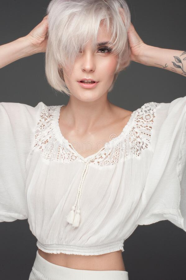 Calm beautiful blonde. In a white blouse. On a dark gray background stock images