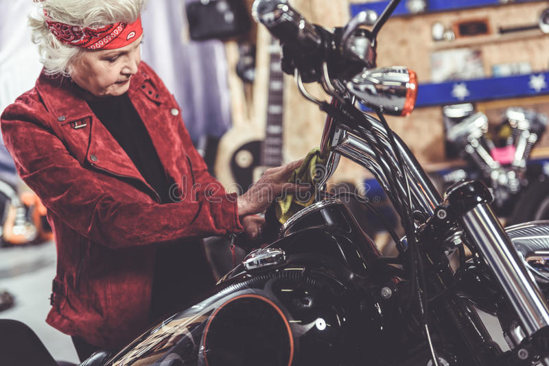 Calm beneficiary burnishing motorcycle in garage. Serene old female cleaning her bike in cosy mechanic shop stock photos