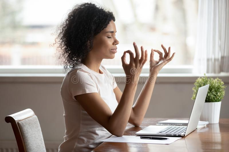 Calm biracial woman meditate near laptop at workplace. Peaceful mixed race ethnicity woman sit at desk work at home distracted meditating at workplace, calm royalty free stock photo