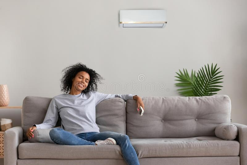 Calm black female relax on couch under air conditioner royalty free stock photo