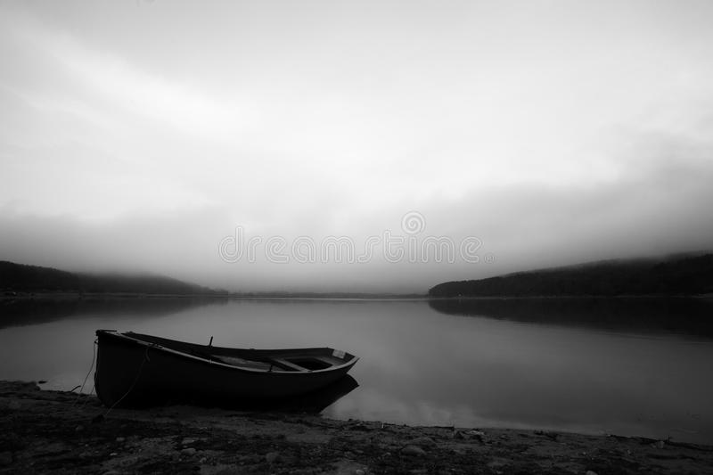 Bw boat. Calm black and white landscape with lake and lonely boat royalty free stock photography