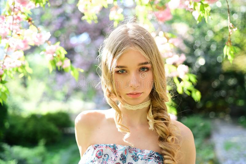 Calm blond girl enjoying spring day in floral garden filled with fresh aroma of flower blossom. Pretty young lady with royalty free stock photography
