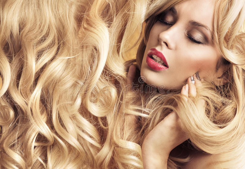 Calm blond lady with tumbling curls stock photo