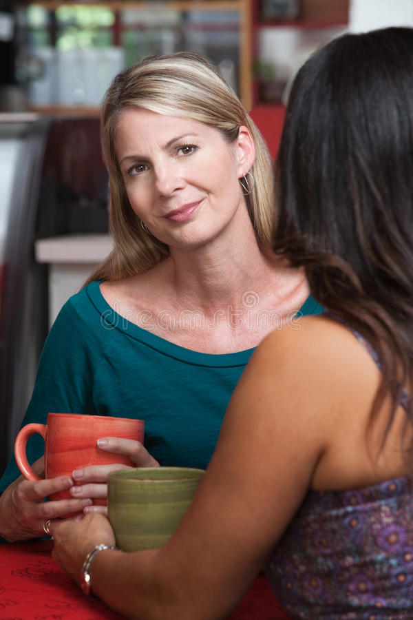 Calm Blond Woman with Friend. Calm blond lady with friend in coffeehouse stock photography