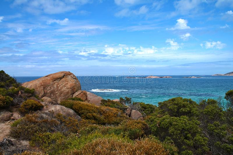 Rocky shoreline with trees and calm blue sea in Western Australia. A calm blue ocean is bordered by green trees and rugged rocks in Esperance, Western Australia royalty free stock photo