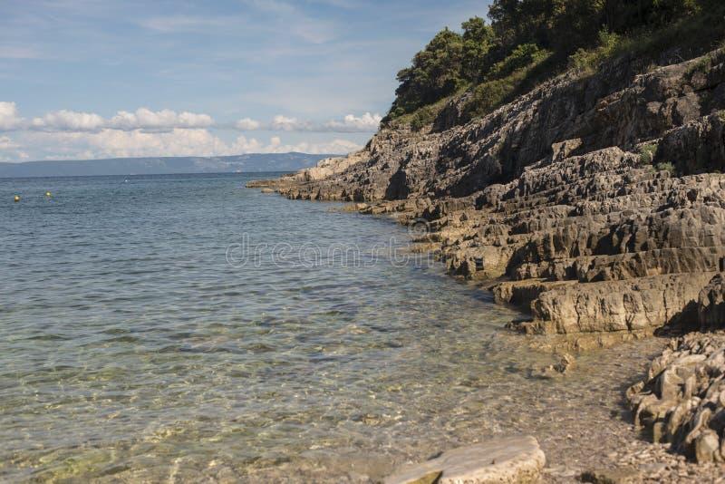 Calm blue sea with pebbles beach royalty free stock photos