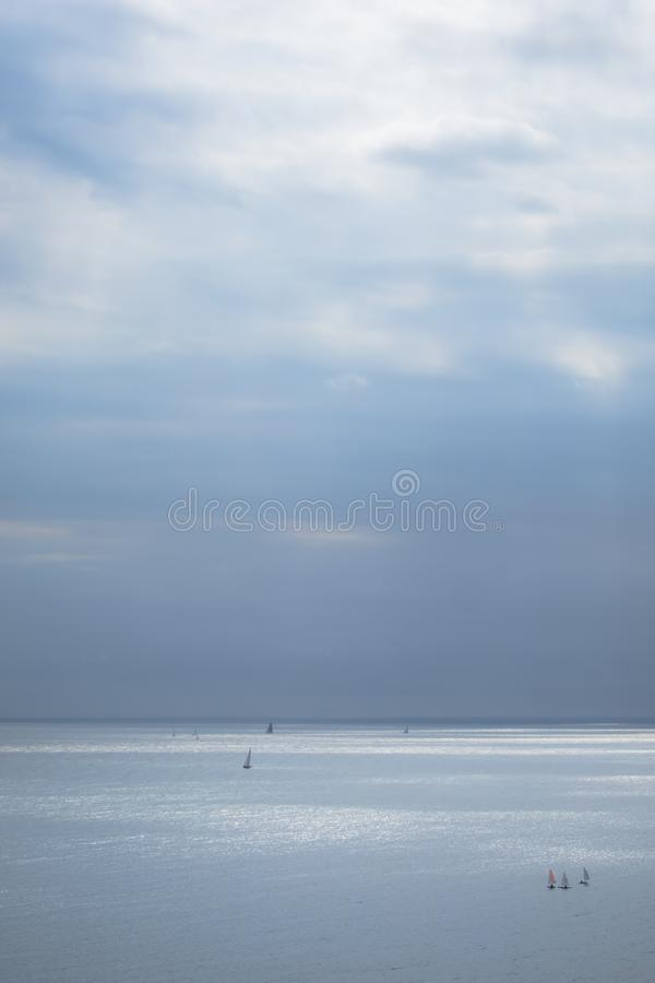 Calm blue sea with sailboats. And cloudy sky stock photography