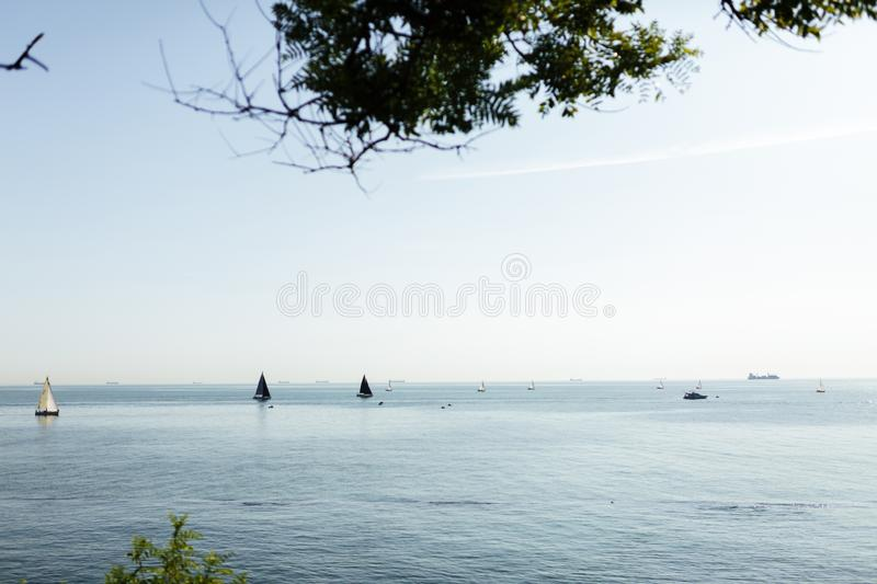 Calm blue sea view with sailboats and ships beyond. Beautiful photo of calm blue sea view with sailboats and ships beyond stock photos