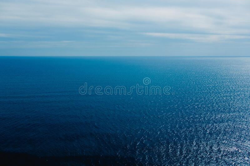 Calm blue sea without waves seen from a cliff with room for text royalty free stock photos