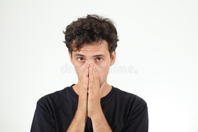 Calm boy in black T-shirt closing his nose. By hands royalty free stock images