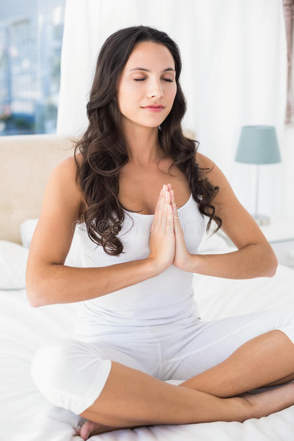 Calm brunette doing yoga on bed. At home in bedroom stock photo