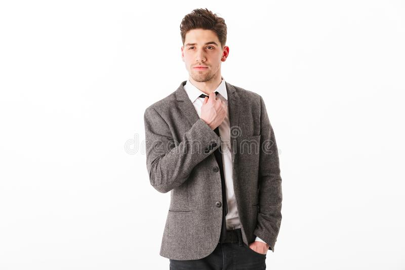 Calm business man in jacket with arm in pocket. Corrects his tie and looking at the camera over white background stock image