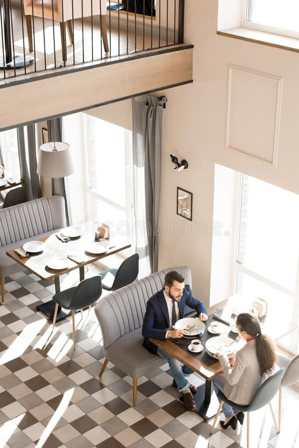 Calm business people eating and resting in restaurant. Directly above view of calm confident business colleagues sitting at table and enjoying tasty food while royalty free stock image