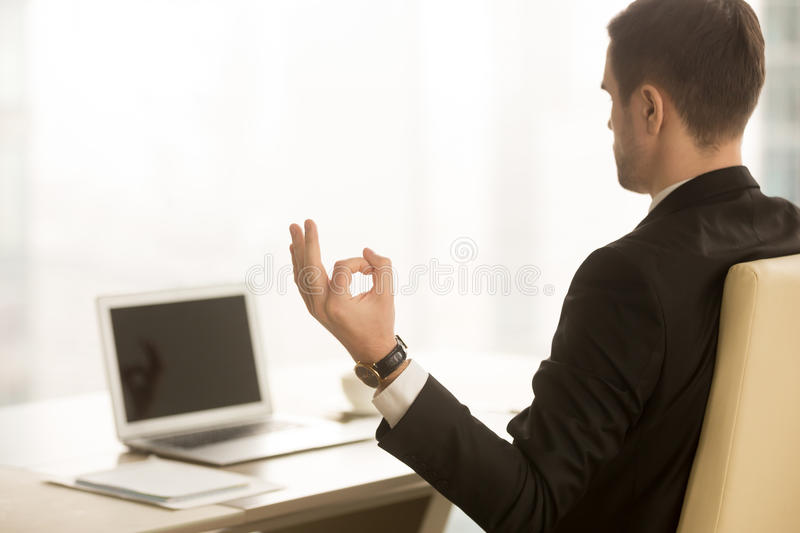 Calm businessman meditating in workplace, chin mudra, yoga at wo royalty free stock photos