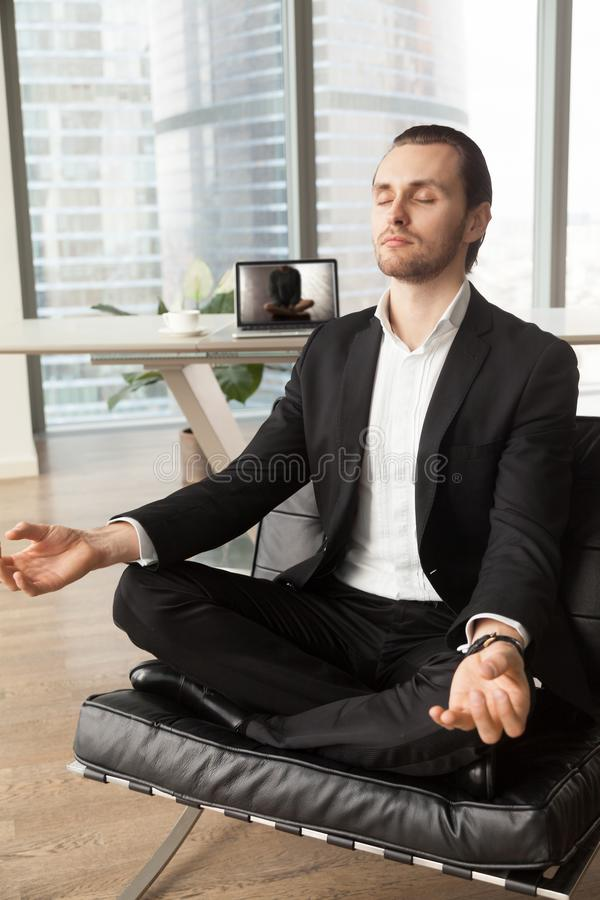 Successful businessman meditating at workplace in modern office. stock photography