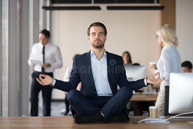 Calm businessman in suit meditating in office on work desk royalty free stock photography