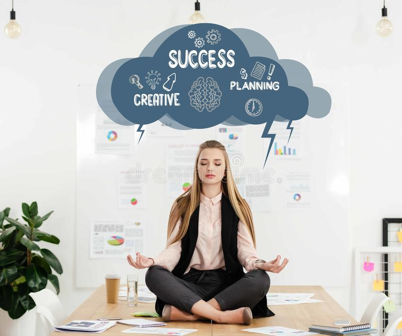 calm businesswoman meditating in lotus position on table in office cloud with creative success planning signs inside stock photo